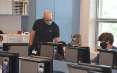 Business teacher Kurt Marx assisting a student.